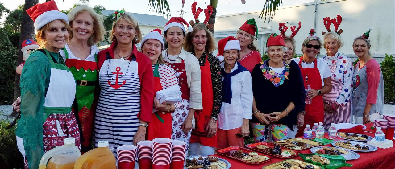 Women standing in front of cookies wearing Christmas costumes