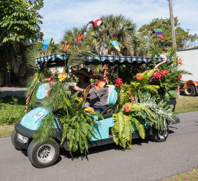 golf cart float decked out in tropical foliage