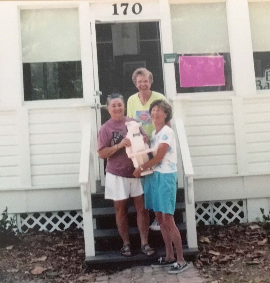 Three women in front of house with house number 170