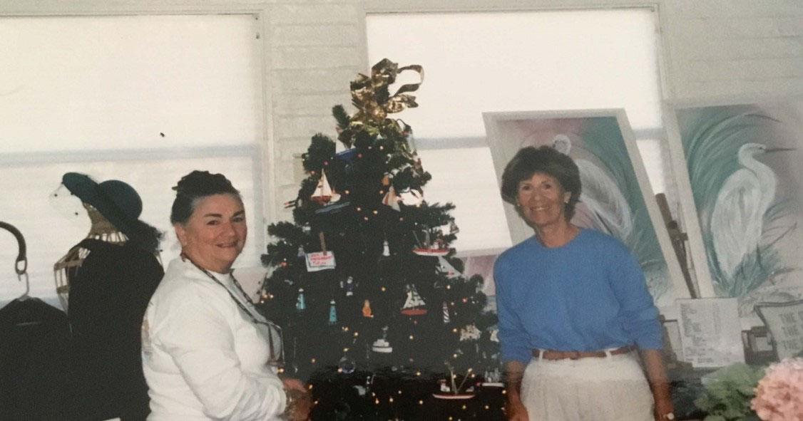 two women next to christmas tree